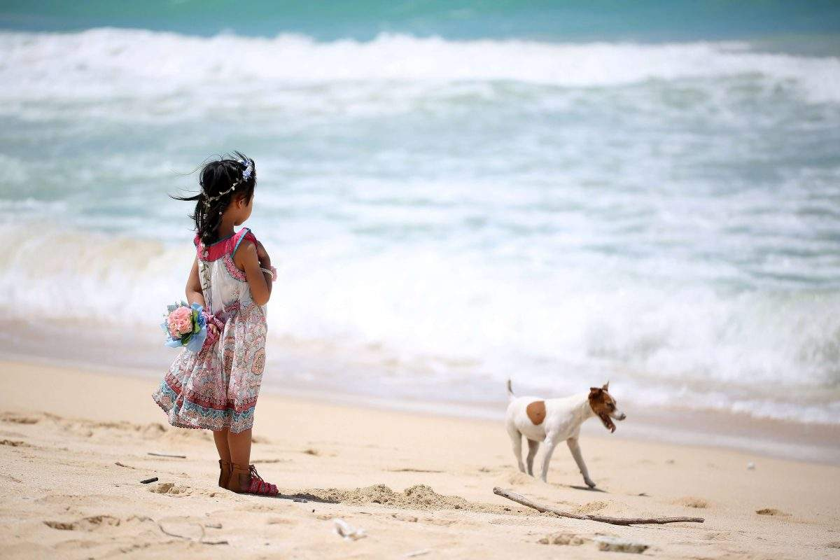 girl with dog in beach