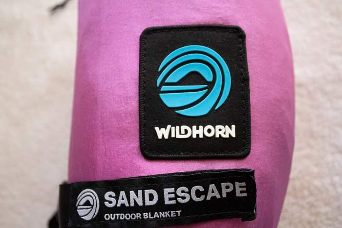 Beach camping tips to bring a sand escape beach blanket like Wildhorn Outfitters